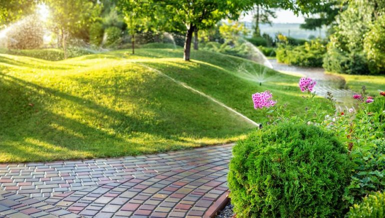 Home irrigation system with different sprinklers installed under the lawn. Landscape design with grassy hills and fruit trees irrigated with smart automatic sprinklers at sunset.
